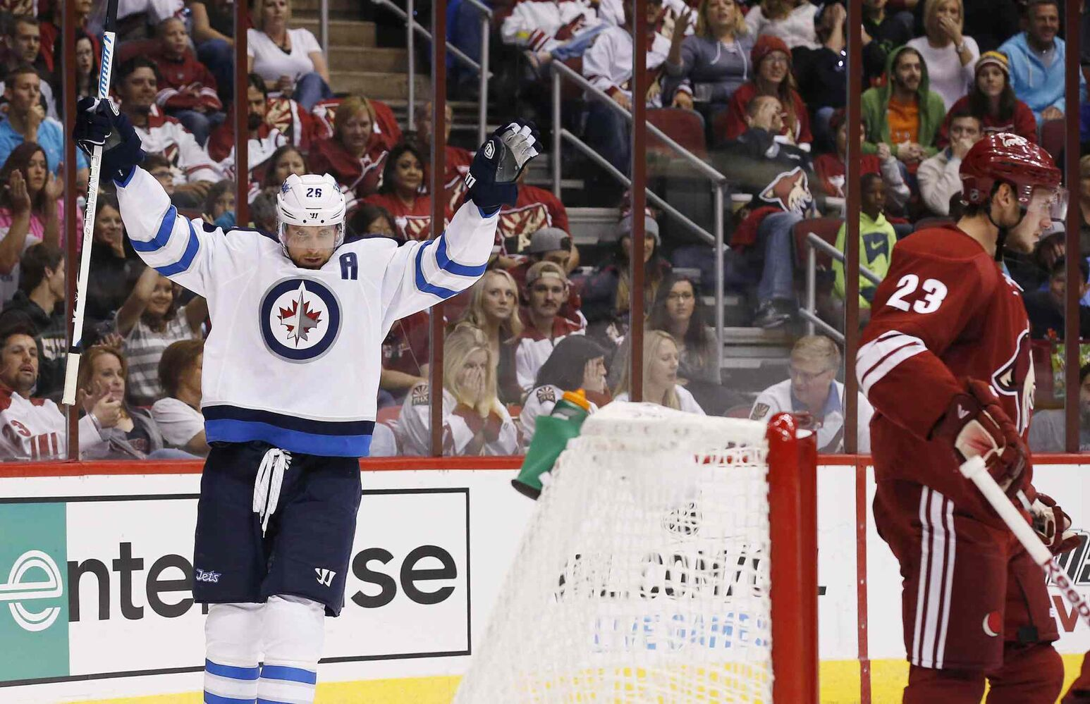 Winnipeg Jets' Blake Wheeler (26) celebrates his goal, the first of two during the first period, against the Arizona Coyotes as Coyotes' Oliver Ekman-Larsson (23), of Sweden, skates in front of the goal area in an NHL hockey game Thursday. (Ross D. Franklin / The Associated Press)
