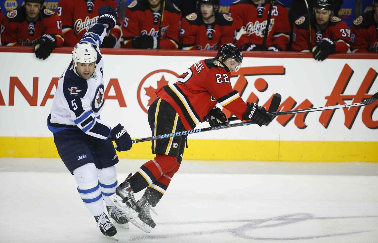 Winnipeg Jets' Mark Stuart, left, knocks Calgary Flames' Lee Stempniak to the ice during the first period. (Jeff McIntosh / The Canadian Press)