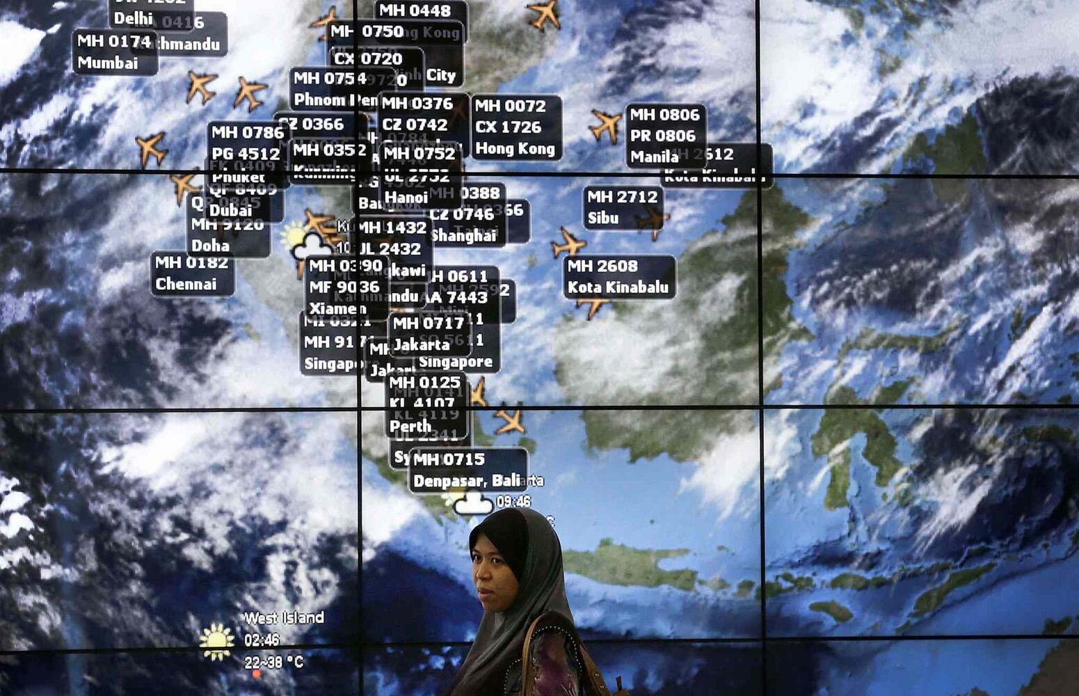 A lady stands in front of an electronic display showing live information of flight positions according to predicted time and flight duration calculations at the Kuala Lumpur International Airport, Sunday, March 16, 2014 in Sepang, Malaysia. Malaysian authorities Sunday were investigating the pilots of the missing jetliner after it was established that whoever flew off with the Boeing 777 had intimate knowledge of the cockpit and knew how to avoid detection when navigating around Asia.