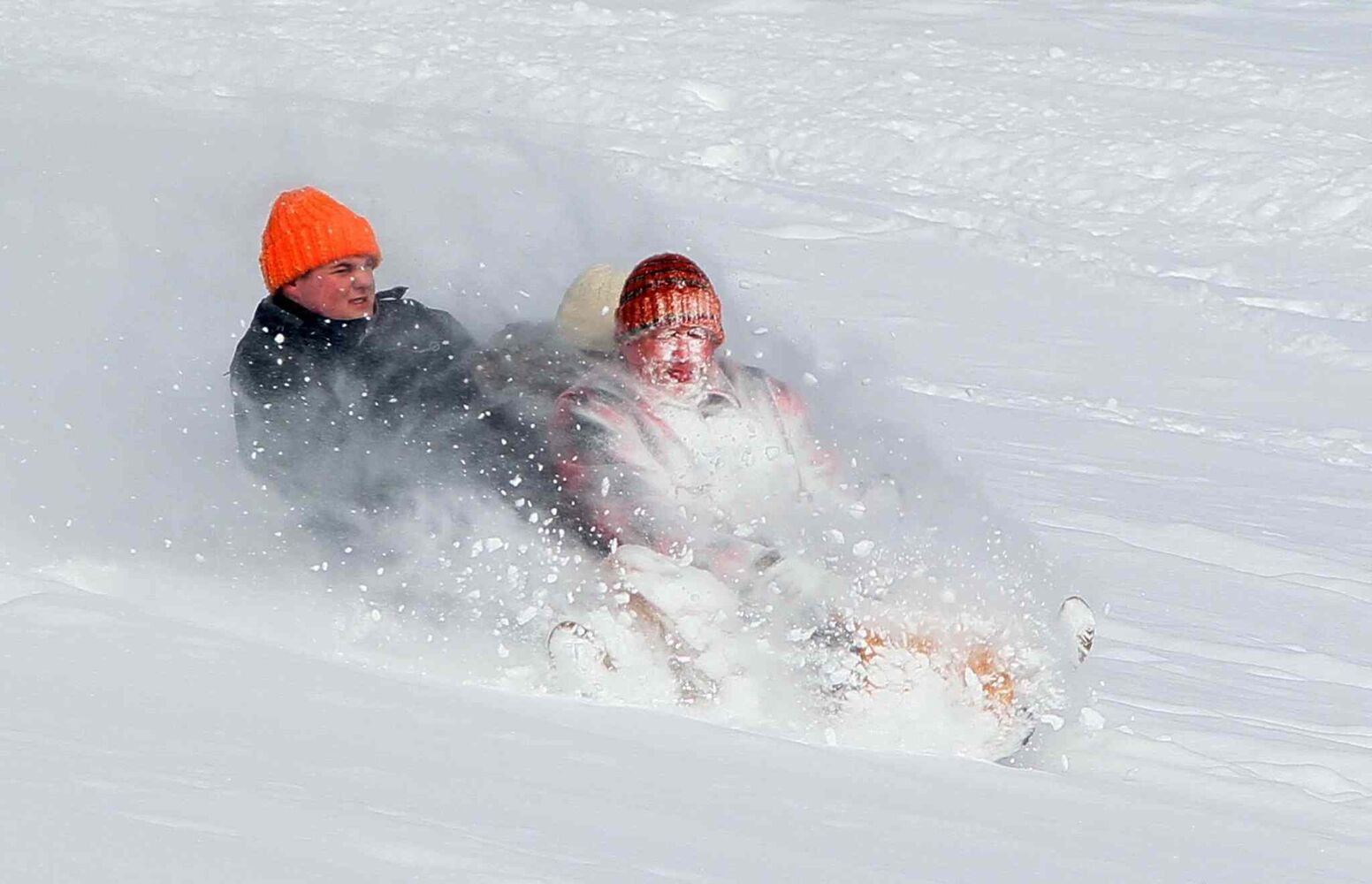 Mark Hachett, right, takes the brunt of the snow as he and his children Kaitlyn, center, and Jacob, left, ride a toboggan at Goodyear Metro Park in Akron, Ohio, on Friday, January 3, 2014.  (Mike Cardew / Tribune Media MCT)