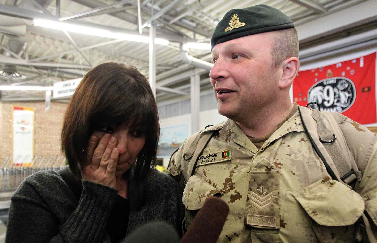 Sgt. David Chelkowski of the 1st RCHA is greeted by his wife Jennifer, who wipes away a tear Monday after greeting her husband at 17 Wing. (Mike Deal / Winnipeg Free Press)
