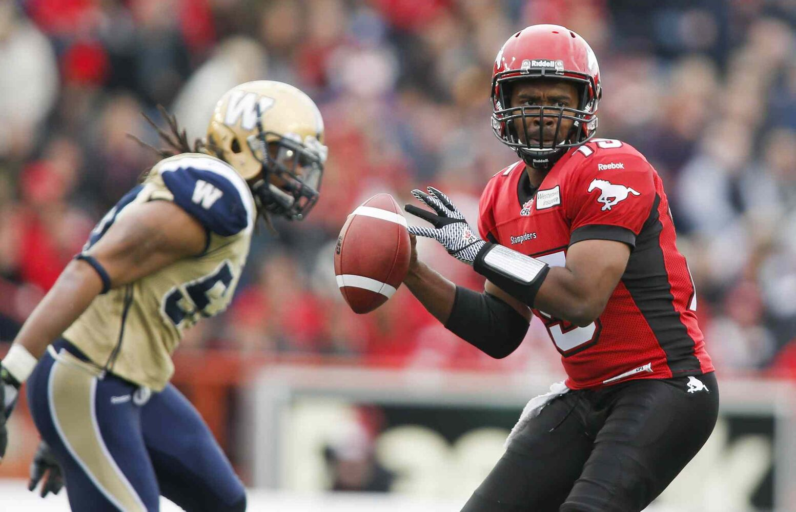 Winnipeg Blue Bombers' Kenny Mainor closes in on Calgary Stampeders' quarterback Kevin Glenn during the first half. (Jeff McIntosh / The Canadian Press)