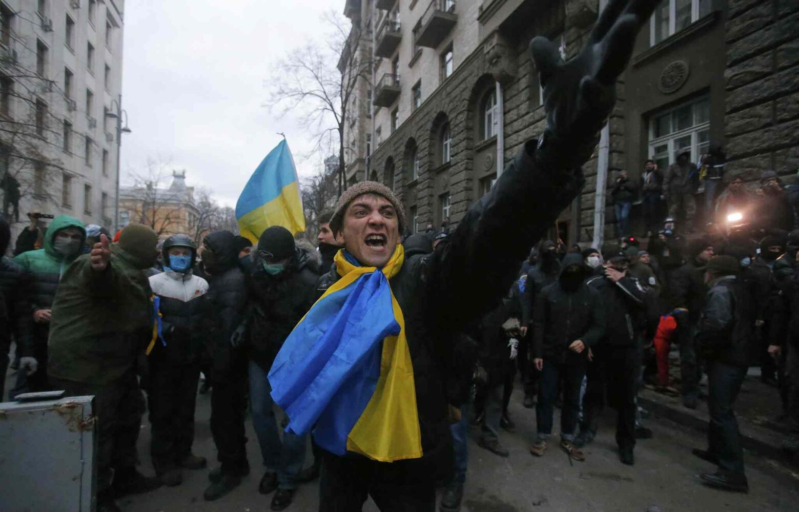 Protesters shout as they clash with police outside of the presidential administration building in downtown Kiev, Ukraine, on Sunday. More than 100,000 demonstrators chased away police to rally in the center of Ukraine's capital on Sunday.  (Sergei Grits / The Associated Press)