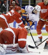 New York Islanders center Mikhail Grabovski (84) shoots against Detroit Red Wings defenseman Niklas Kronwall, top left, of Sweden, and goalie Petr Mrazek during the first period of an NHL hockey game, Saturday, Jan. 31, 2015, in Detroit. (AP Photo/Carlos Osorio)