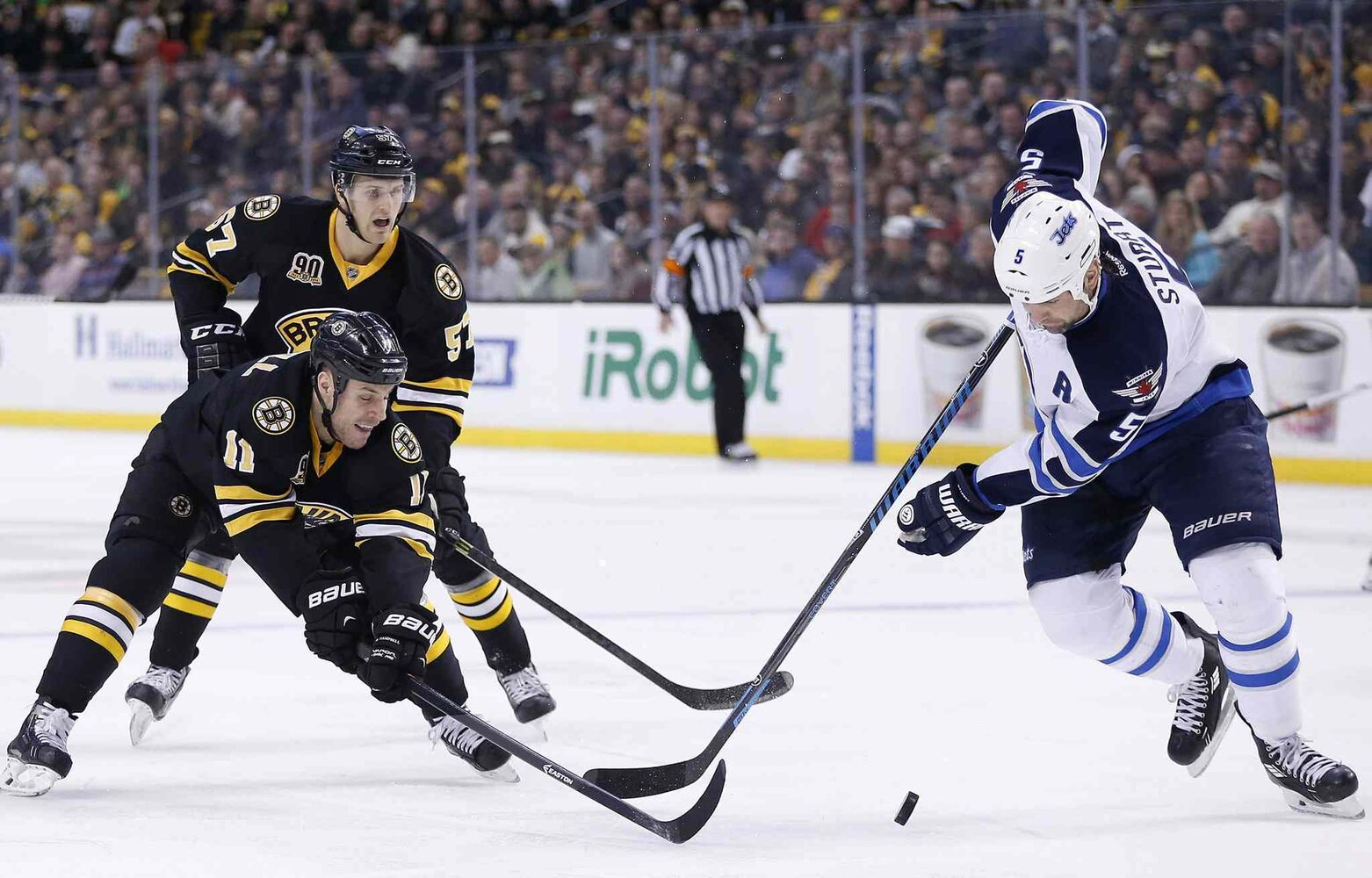 Boston Bruins' Gregory Campbell (11) and Winnipeg Jets' Mark Stuart (5) battle for the puck in the second period of an NHL hockey game in Boston Saturday.