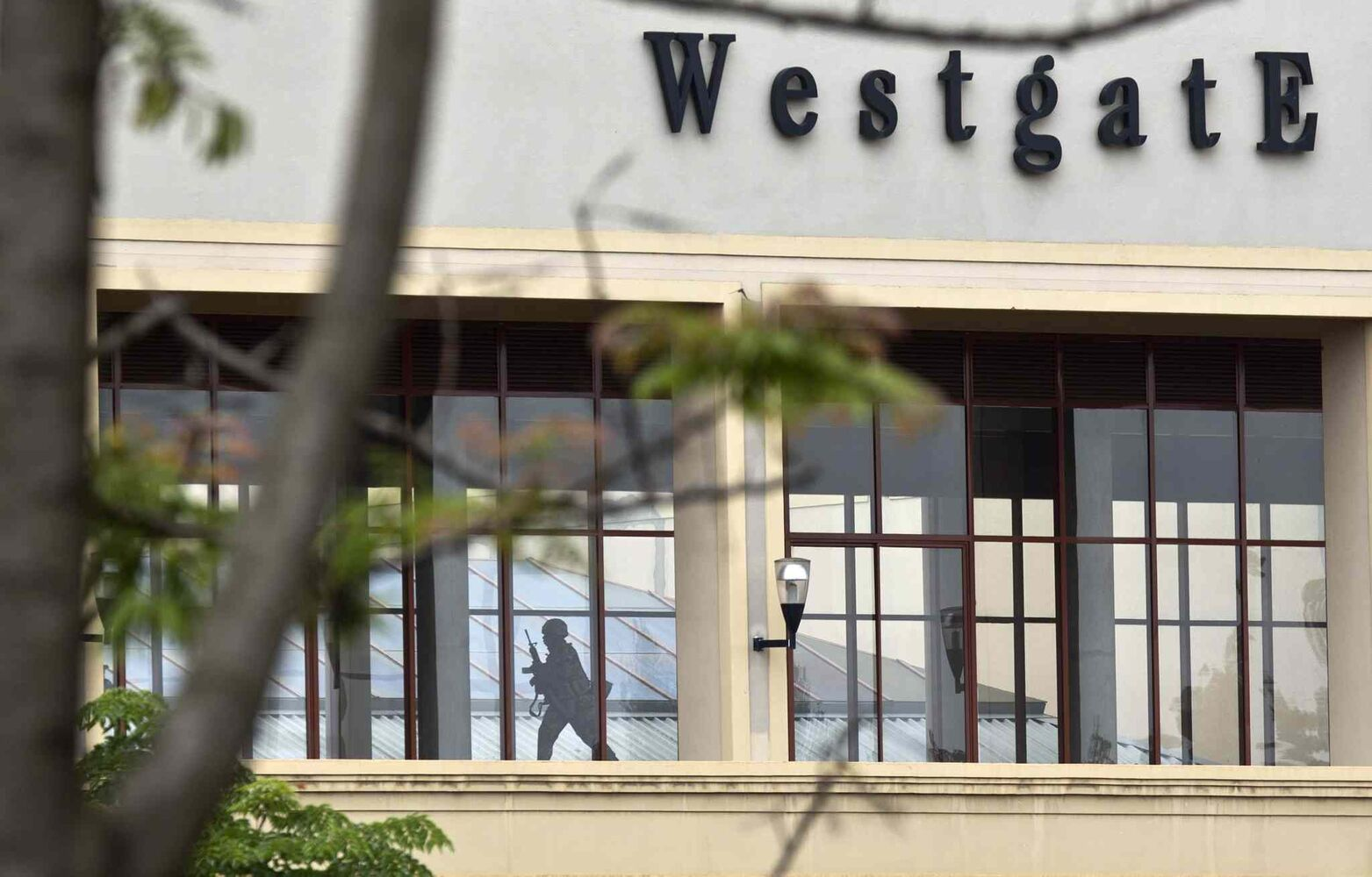 A Kenyan soldier runs through a corridor on an upper floor, shortly before an explosion was heard, at the Westgate Mall in Nairobi, Kenya Tuesday.