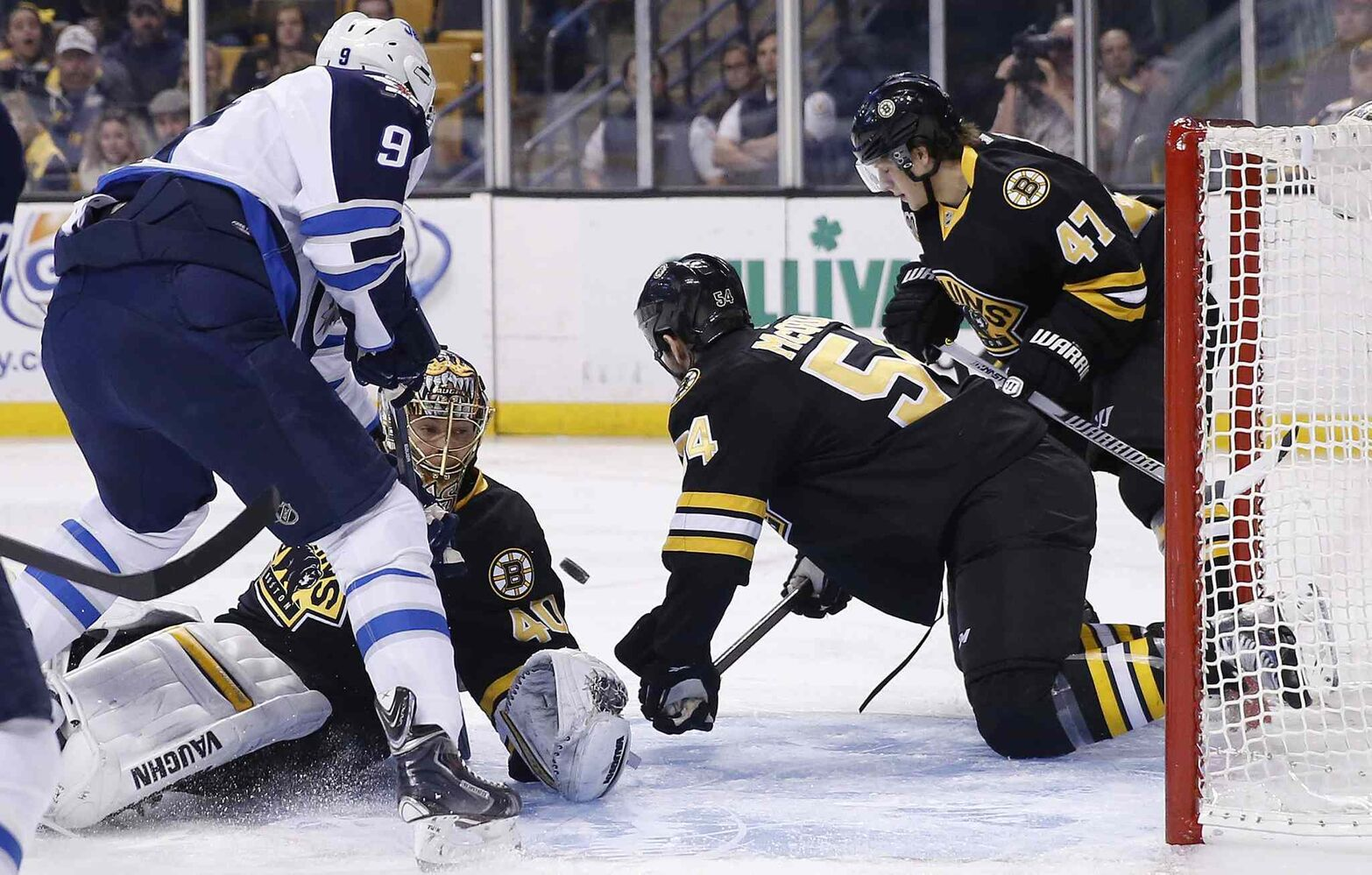 Winnipeg Jets' Evander Kane (9) looks for the rebound as the puck deflects off of Boston Bruins' Tuukka Rask (40) while the Bruins' Adam McQuaid (54) and Torey Krug (47) defend in the first period. (Michael Dwyer / The Associated Press)