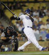 Los Angeles Dodgers' Carl Crawford, center follows through on his hit for a walk off double to score Los Angeles Dodgers' Chone Figgins during the 10th inning of a baseball game against the Detroit Tigers in Los Angeles, Tuesday, April 8, 2014. The Los Angeles Dodgers won 3-2. (AP Photo/Kelvin Kuo)