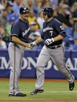 Milwaukee Brewers' Mark Reynolds (7) shakes hands with third base coach Ed Sedar after hitting a home run off Tampa Bay Rays starting pitcher Jake Odorizzi during the third inning of an interleague baseball game Monday, July 28, 2014, in St. Petersburg, Fla. (AP Photo/Chris O'Meara)