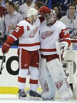 Detroit Red Wings defenseman Niklas Kronwall (55), of Sweden, celebrates with goalie Petr Mrazek, of the Czech Republic, after Detroit defeated the Tampa Bay Lightning 3-2 during Game 1 of an NHL hockey first-round playoff series Thursday, April 16, 2015, in Tampa, Fla. (AP Photo/Chris O'Meara)
