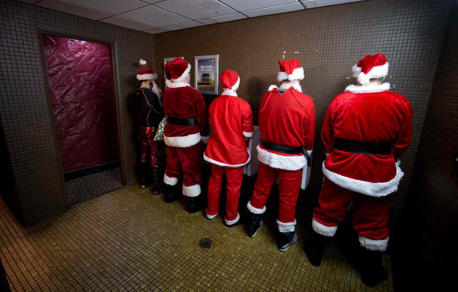 Men dressed as Santa Claus use the washroom at a bar during a Santacon event in Vancouver, B.C. on Saturday. (DARRYL DYCK / THE CANADIAN PRESS)