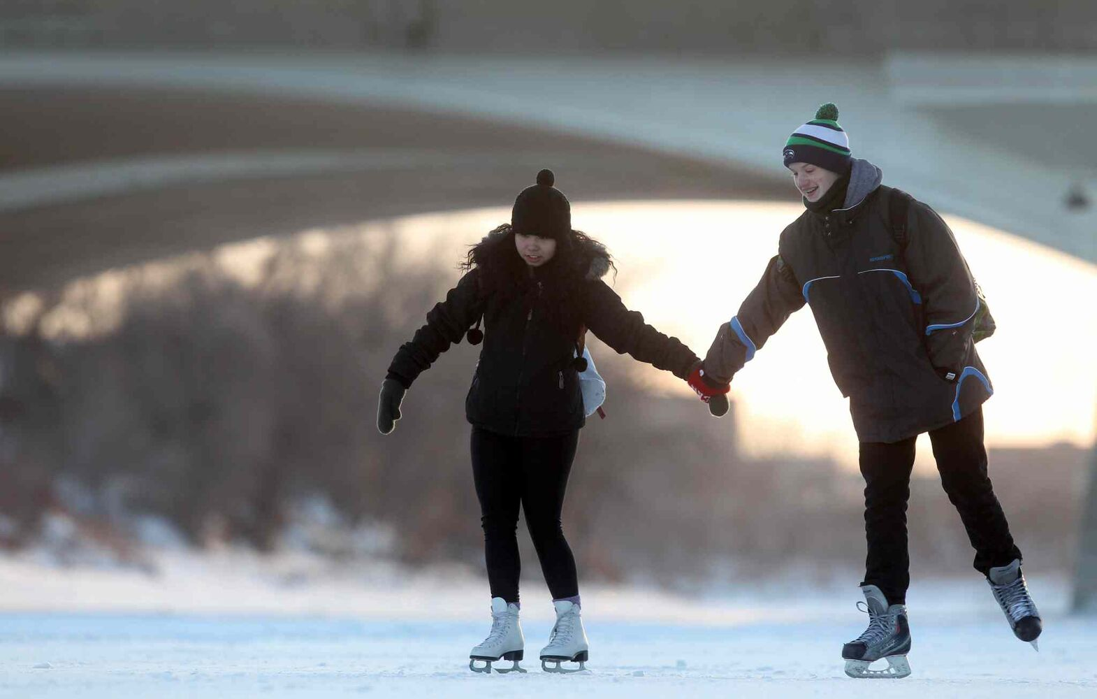 Desirae Lavallee and Jayden Bannerman enjoy skating together along the Red River on the newly opened River Trail Thursday.  (Ruth Bonneville / Winnipeg Free Press)