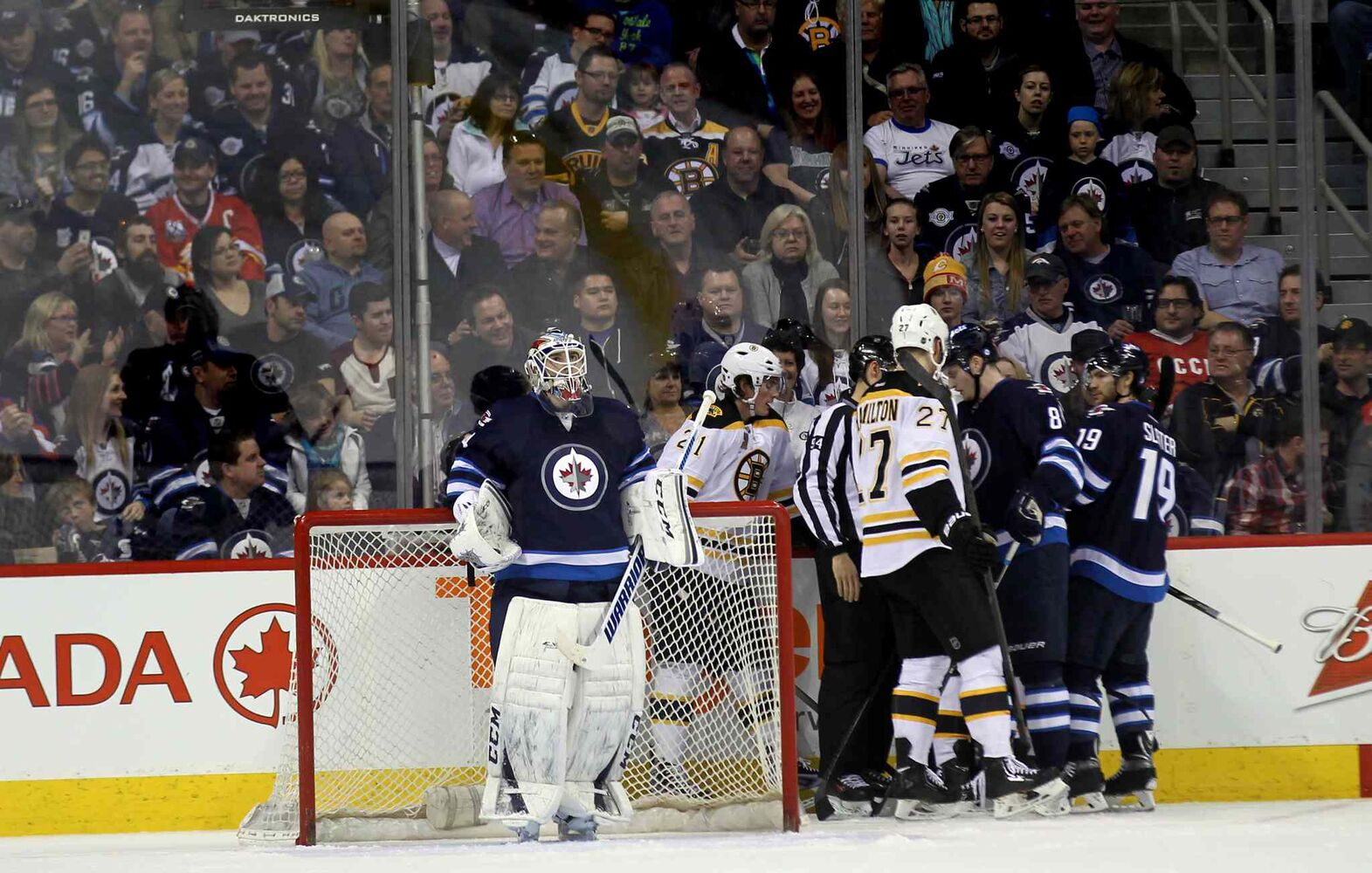 Winnipeg net-minder Michael Hutchinson watches the replay while other players sort it out behind the net during the second period of Thursday's game. (Phil Hossack / Winnipeg Free Press)