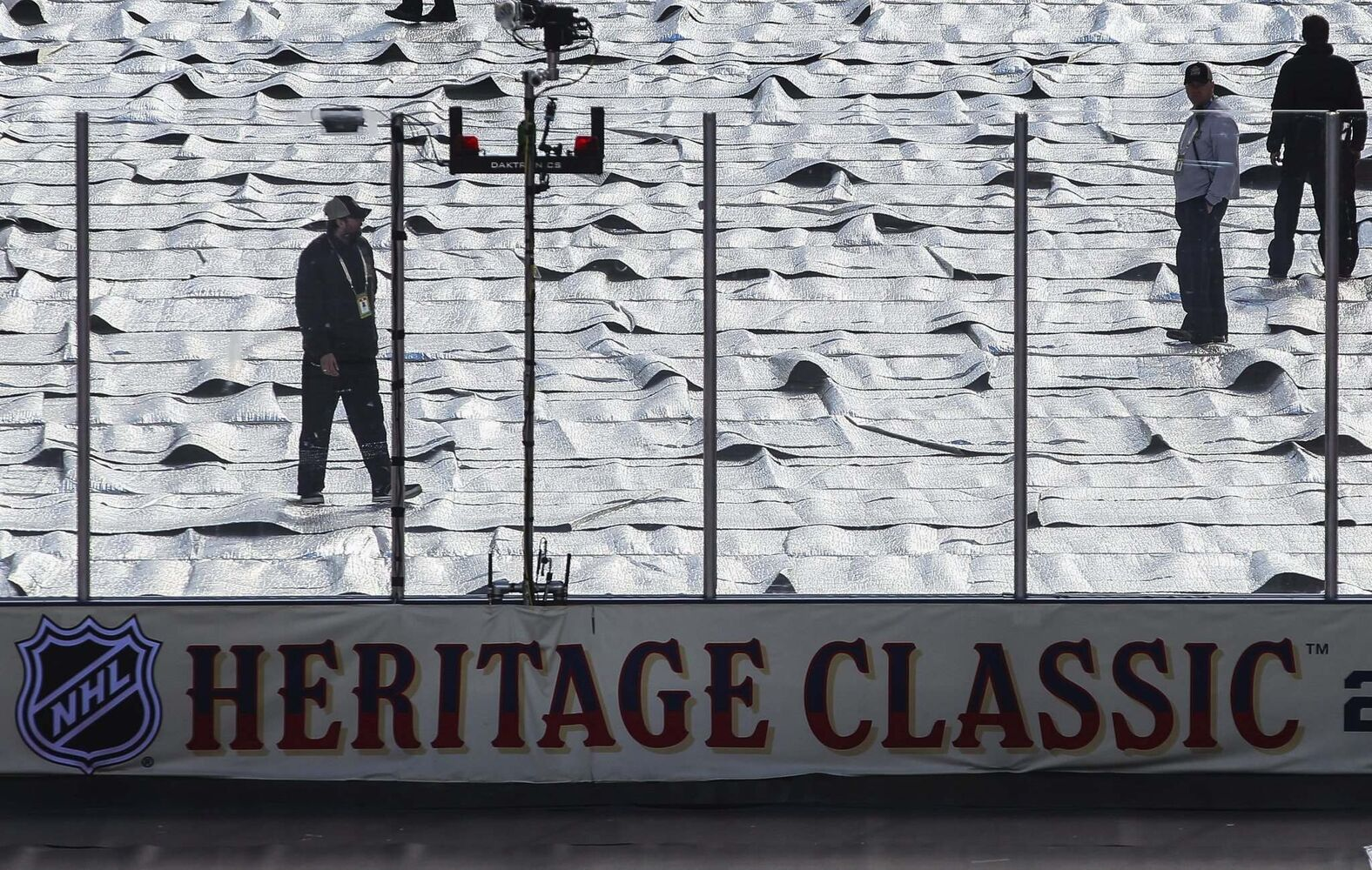 Rink maintenance staff keep an eye on the ice before the NHL game between the Winnipeg Jets and the Edmonton Oilers at Investors Group Field. Glare delayed the beginning of the game, rescheduled to begin at 3:53 p.m.</p> (MIKE DEAL / WINNIPEG FREE PRESS)