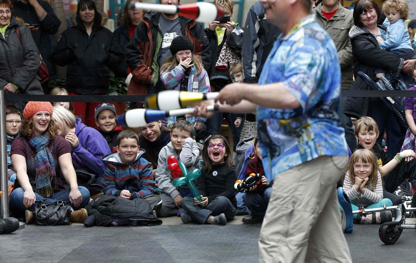 Kids of all ages enjoy a performance Monday by North Vancouver juggler Mike Battie at the Manitoba Childrens Festival's Festival of Fools at the Forks Market. The festival offers shows every day this week between 11 a.m. to 3 p.m.,  featuring face painting, jugglers, clowns, acrobats, swinging trapeze and craft workshops. (KEN GIGLIOTTI / WINNIPEG FREE PRESS)