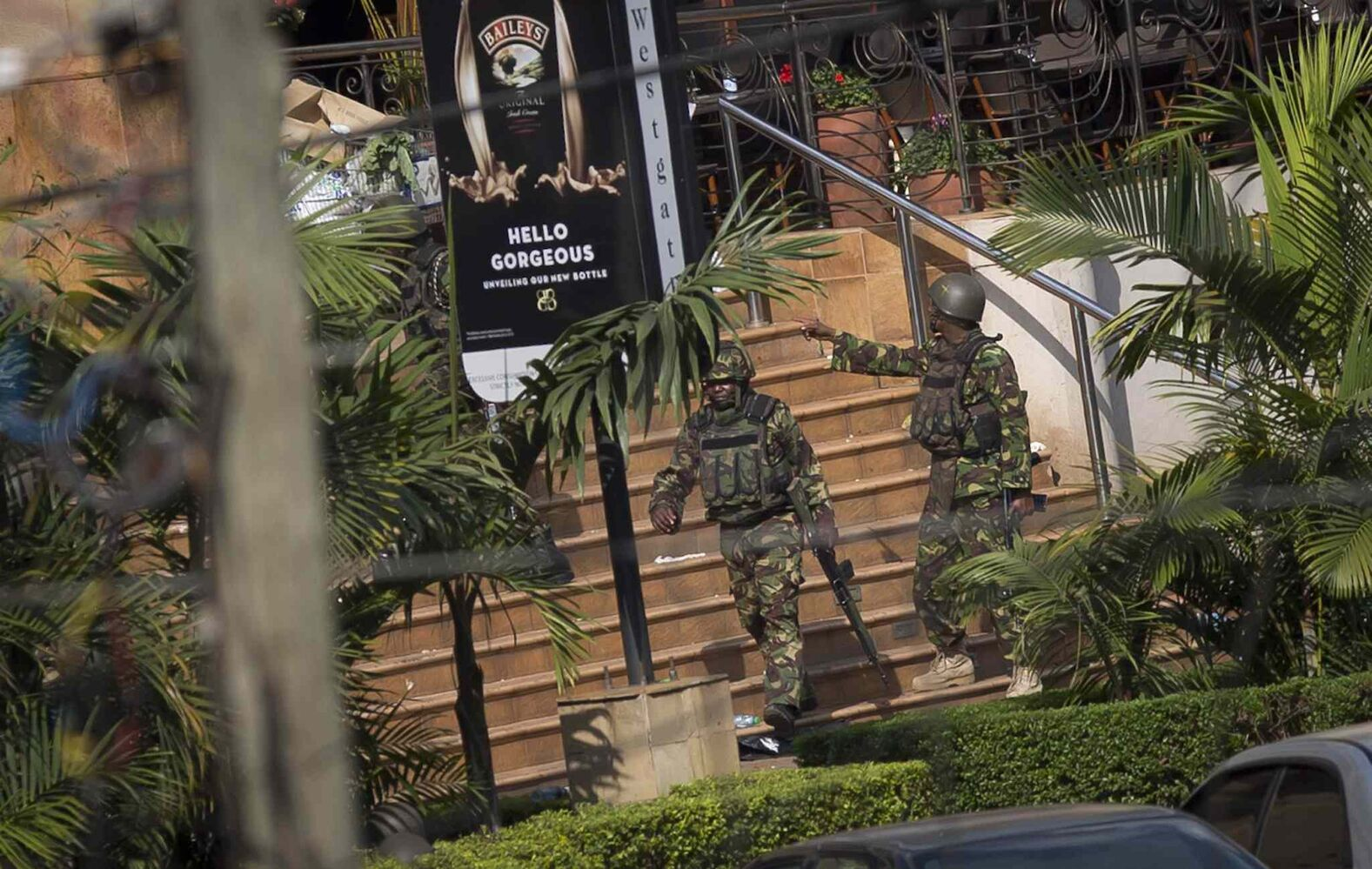 Soldiers from the Kenya Defence Forces walk out, following the sound of explosions and gunfire, from the Westgate Mall in Nairobi, Kenya, Sunday. Kenyan military forces engaged in sporadic gun battles Sunday with the Islamic extremists holding an unknown number of hostages inside an upscale Nairobi mall, as officials said the death toll from a grenade-and-gunfire siege a day earlier rose to 59, with at least 175 wounded.