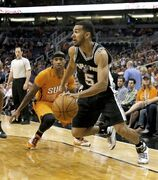 San Antonio Spurs guard Cory Joseph (5) drives by Phoenix Suns guard Isaiah Thomas (3) in the first quarter during an NBA basketball game, Friday, Oct. 31, 2014, in Phoenix. (AP Photo/Rick Scuteri)