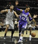 Sacramento Kings guard Ben McLemore, right, chases the loose ball against San Antonio Spurs forward Tim Duncan during the first half of an NBA basketball game, Friday, Nov. 28, 2014, in San Antonio. (AP Photo/Darren Abate)