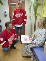Detroit Red Wings NHL hockey players Gustav Nyquist, left, and Joakim Andersson visit with Keira Van Dixhoorn, 11, of Roscommon, Mich., on the pediatric floor of Covenant HealthCare in Saginaw, Mich., Wednesday, Sept. 17, 2014. Five members of the Red Wings, Luke Glendening, Brendan Smith, Riley Sheahan, Gustav Nyquist and Joakim Andersson are touring Michigan on a preseason caravan. (AP Photo/The Saginaw News, Jeff Schrier) ALL LOCAL TELEVISION OUT; LOCAL TELEVISION INTERNET OUT