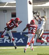 Winnipeg Blue Bombers' Clarence Denmark goes up to catch a pass in front of Calgary Stampeders' Demetrice Morley (left) and Keon Raymond at McMahon Stadium in Calgary Saturday.