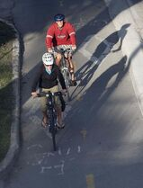 Cyclists on Assiniboine Avenue at Donald Street enjoy a cool morning ride Tuesday.