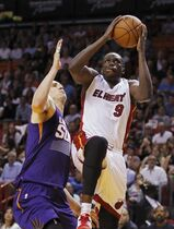 Miami Heat forward Luol Deng shoots during the first quarter under pressure from Phoenix Suns guard Gerald Green during an NBA basketball game, Monday, March 2, 2015, in Miami. (AP Photo/Joe Skipper)