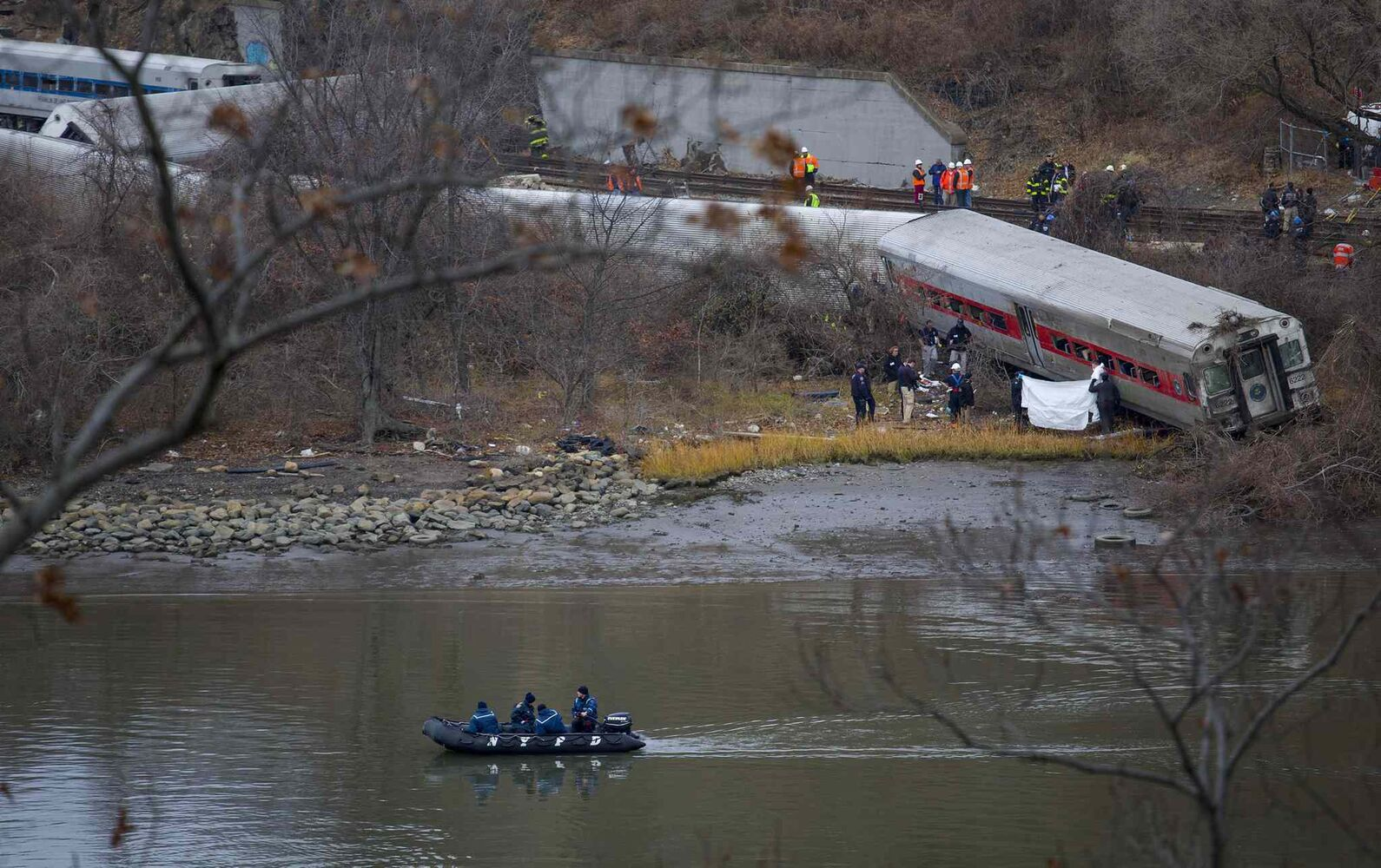 Viewed from Manhattan, first responders and others work near a victim next to a derailed Metro North passenger train.