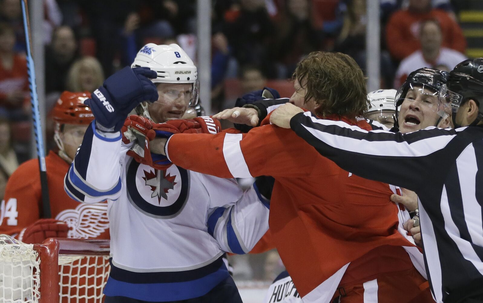 Jets defenseman Jacob Trouba mixes it up with the Red Wings Justin Abdelkader. (Carlos Osorio / The Associated Press)