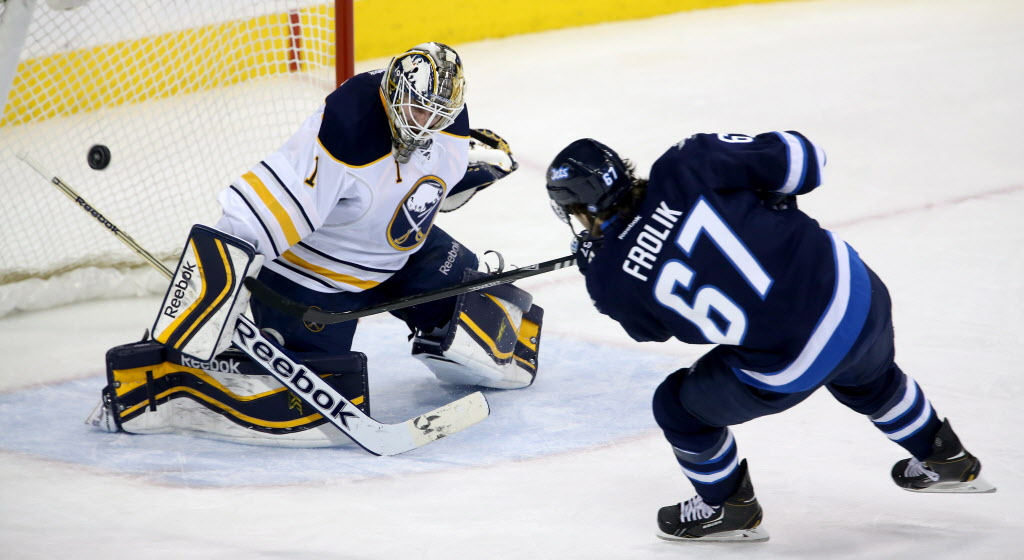 Winnipeg Jets' Michael Frolik (#67) can't put the puck past Buffalo Sabres' goaltender Jhonas Enroth (#1) during third period at the MTS Centre Tuesday.  (Trevor Hagan / The Canadian Press)