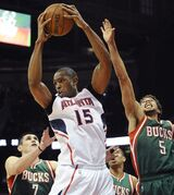 Atlanta Hawks' Al Horford (15) pulls down a rebound over Milwaukee Bucks' Ersan Ilyasova (7) and Michael Carter-Williams (5) in the first half of an NBA basketball game Monday, March 30, 2015, in Atlanta. (AP Photo/David Tulis)