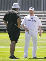Oakland Raiders owners Mark Davis, right, laughs on the sideline with general manager Reggie McKenzie, left, during their NFL football training camp on Friday, July 25, 2014, in Napa, Calif. (AP Photo)