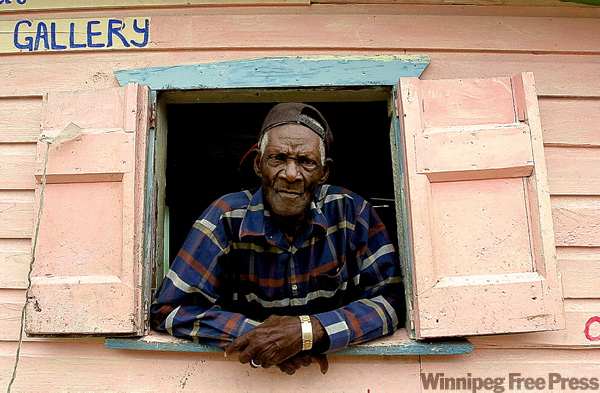 Artist Canute Calliste looks out the window from his gallery in L'Esterre, Carriacou.