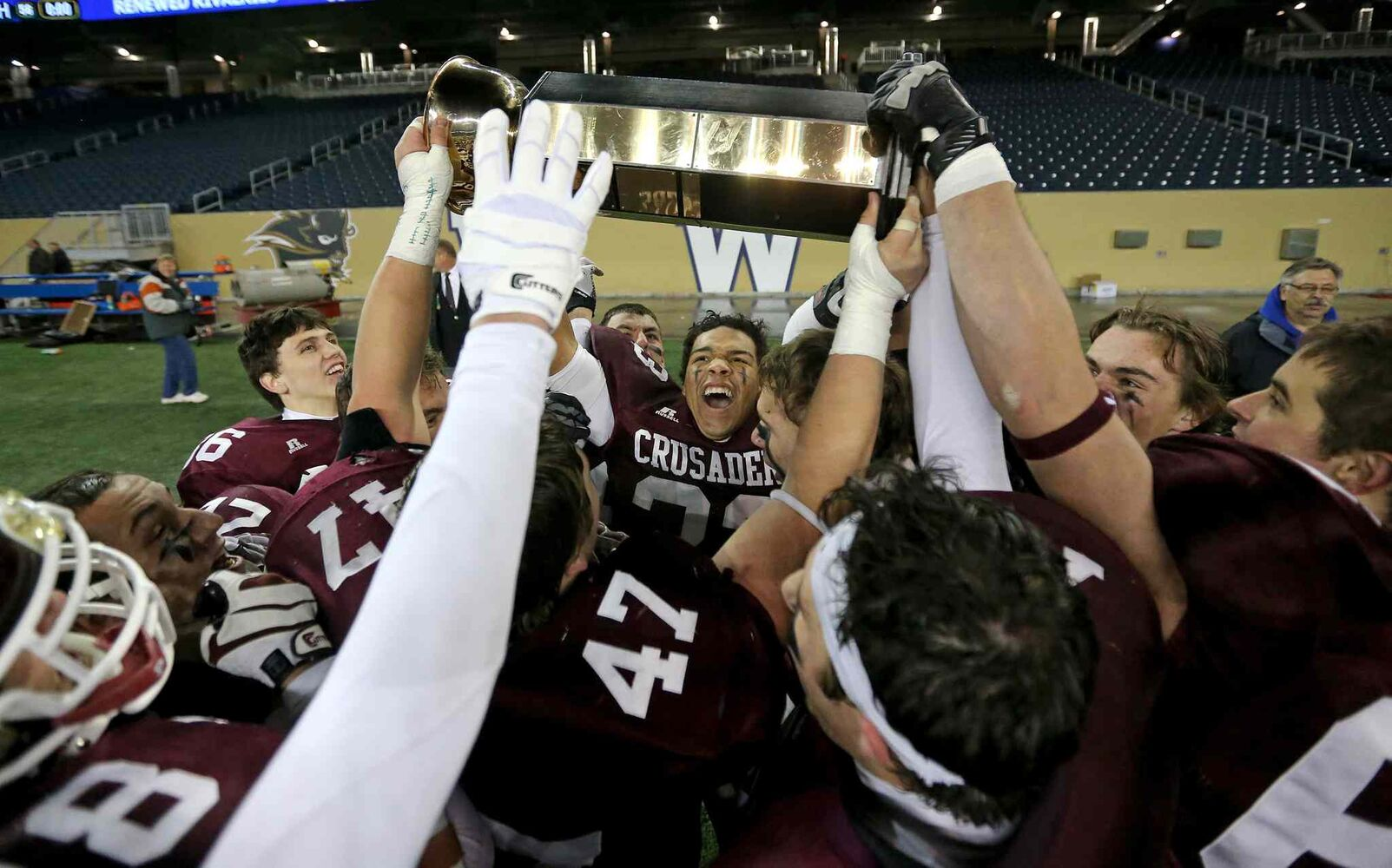 The St. Paul's Crusaders hoist the hardware. (Trevor Hagan / Winnipeg Free Press)