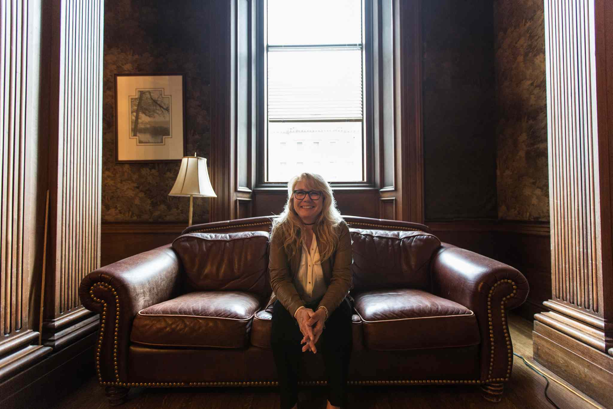 Cindy Tugwell, Executive Director for Heritage Winnipeg, sits on a leather couch in the 'tapestry room' of the Millennium Centre.