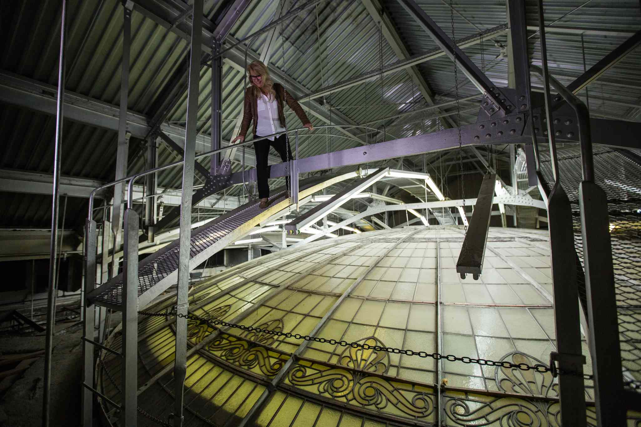 Cindy Tugwell, Executive Director for Heritage Winnipeg, on the catwalk above the glass dome in the Millennium Centre.