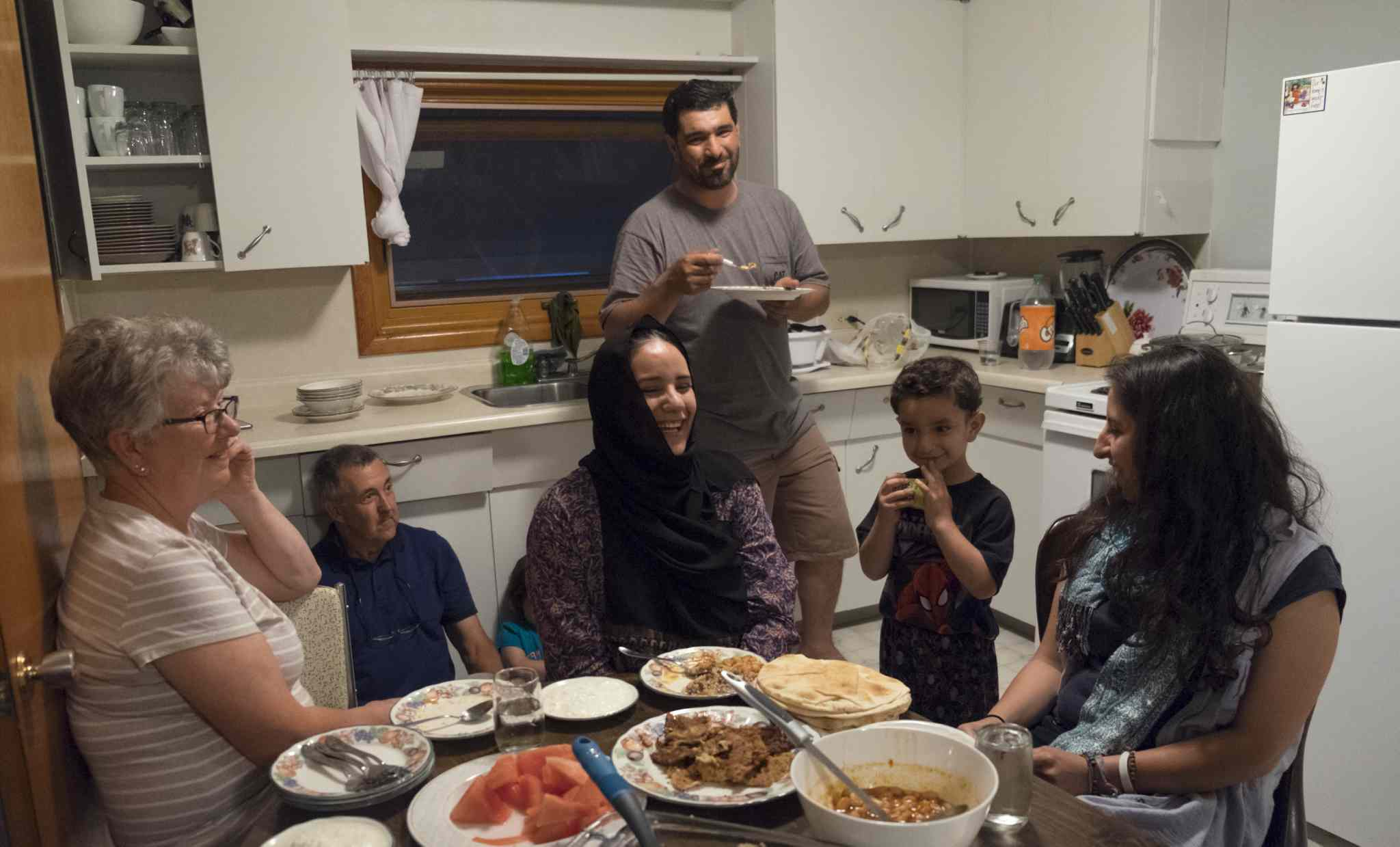 The sponsors and families have grown close over the past four months and often spend time together. Here they break fast during the Holy month of Ramadan.