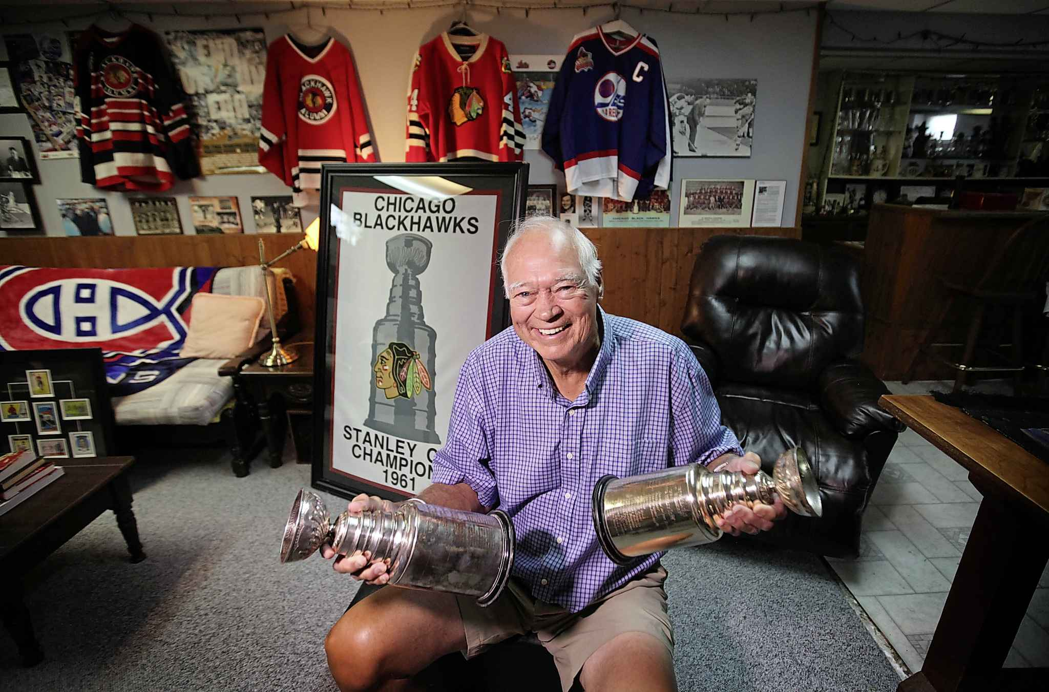 Ab McDonald in his basement with his memorabilia including two replica Stanley Cups from the 1960 Montreal Canadiens and the 1961 Chicago Blackhawks. Ab has been on four Stanley Cup-winning teams, three in Montreal and one in Chicago. He was raised in Winnipeg and was the first-ever captain of the original Winnipeg Jets.