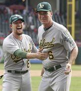 Oakland Athletics manager Bob Melvin (6) and shortstop Jed Lowrie (8) celebrates after a baseball game against the Texas Rangers on Sunday, Sept. 28, 2014, in Arlington, Texas. The A's clinched a playoff spot wiht a 4-0 win over the Rangers. (AP Photo/LM Otero)