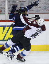 Big Buff sends Colorado's Jan Hejda flying during first-period action in Winnipeg on Sunday.