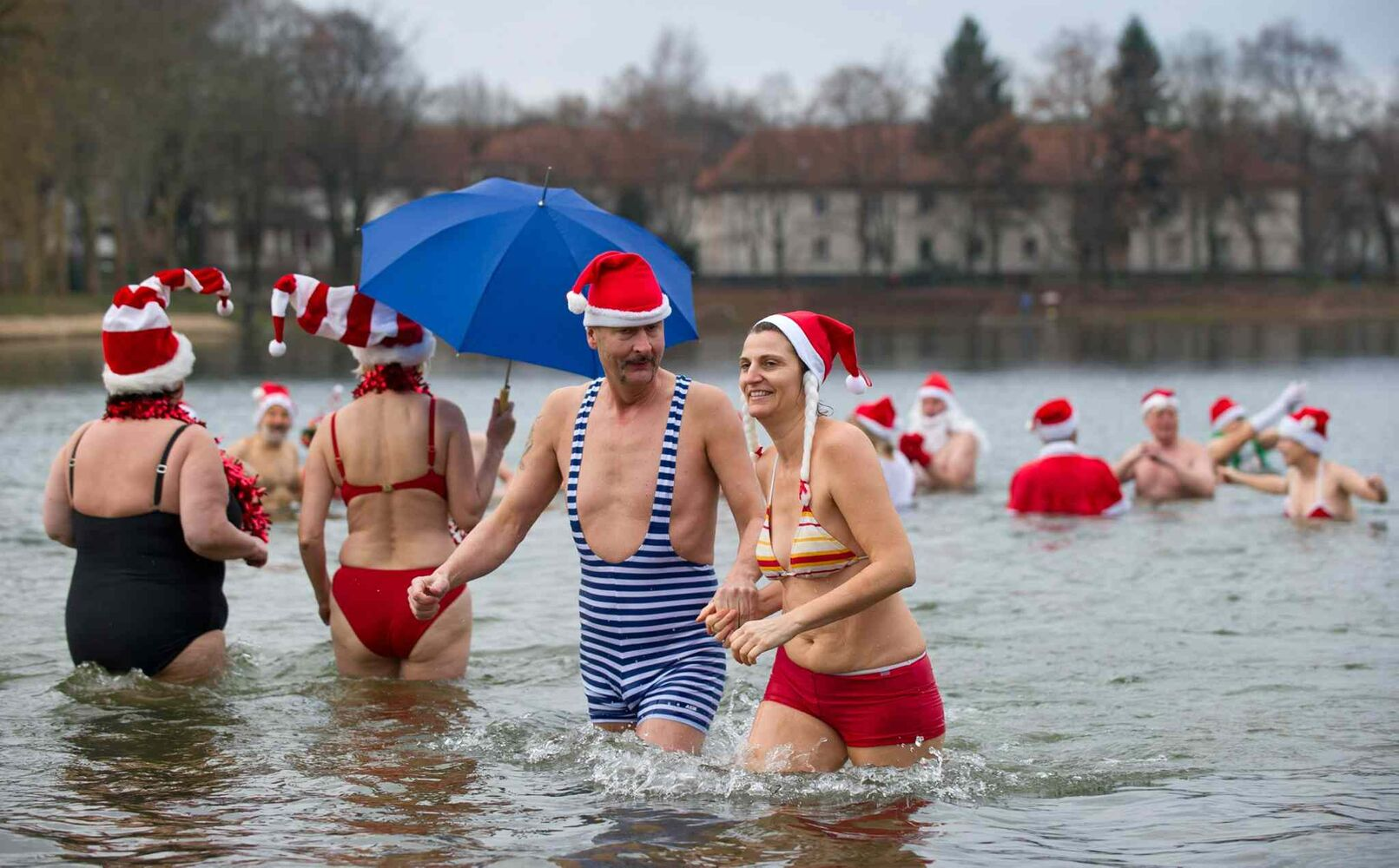 Costumed members of the Berlin Seals go to swim  in Lake Orankesee in Berlin, Germany Wednesday. Traditionally, the group meets  for swimming on Christmas Day.  (The Associated Press)