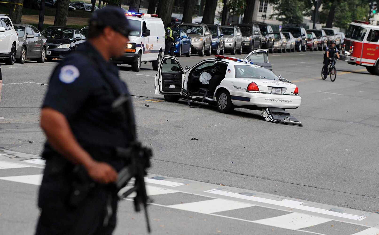 A U.S. Capitol police car sits wrecked in the street as an officer surveys the scene. (Olivier Douliery / MCT)