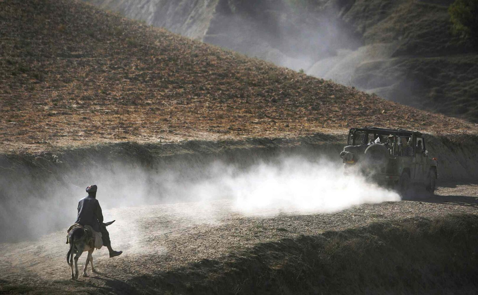 Sept. 15, 2009: An Afghan man on his donkey follows a convoy of German ISAF soldiers patrolling Yaftal E Sofla, in the mountainous region of Feyzabad, east of Kunduz, Afghanistan. (Anja Niedringhaus / The Associated Press)