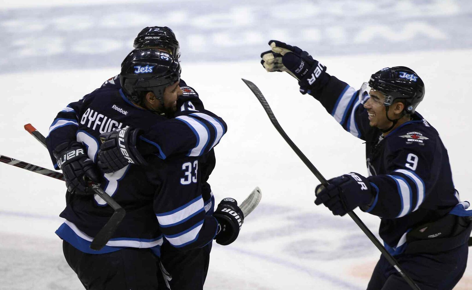Winnipeg Jets defenceman Dustin Byfuglien (left) celebrates with Olli Jokinen and Evander Kane (right) during the third period after scoring the Jets' second goal to tie the game. (JOE BRYKSA / WINNIPEG FREE PRESS)