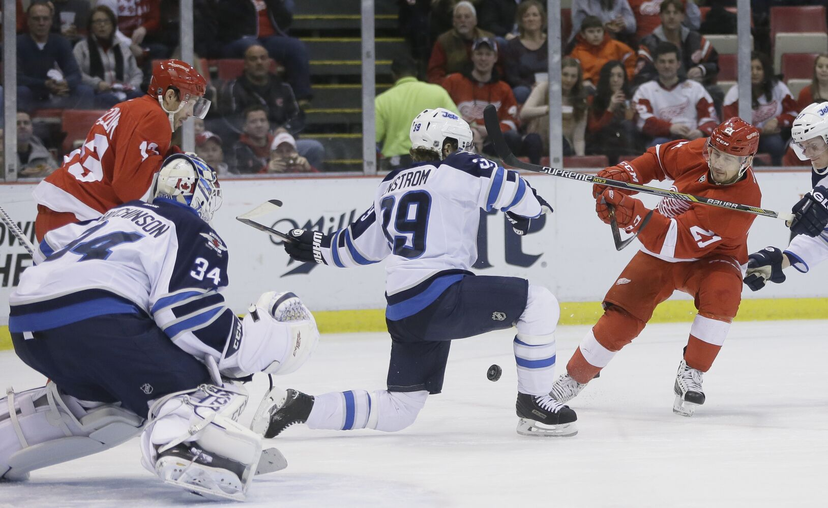 Toby Enstrom (centre) drops in front of a shot by Red Wings forward Tomas Tatar.  (Carlos Osorio / The Associated Press)