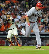 Los Angeles Angels outfielder Mike Trout, right, runs to first on a pass ball strikeout as Houston Astros catcher Hank Conger makes the throw in the fifth inning of a baseball game, Saturday, April 18, 2015, at Minute Maid Park in Houston. (AP Photo/Eric Christian Smith)