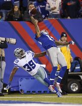 FILE - In this Nov. 23, 2014, file photo, New York Giants wide receiver Odell Beckham Jr. (13) makes a one-handed catch for a touchdown against Dallas Cowboys cornerback Brandon Carr (39) in the second quarter of an NFL football game in East Rutherford, N.J. The one-handed catch by Odell Beckham Jr. that became the most talked-about play from Sunday, Nov. 23, 2014, did more than just boost his standing with the Giants, it paid off a routine growing popular among many skill players of practicing the impractical, one-handed circus grab. (AP Photo/Kathy Willens, File)