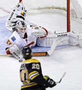 Calgary Flames goalie Karri Ramo drops to the ice to make a save by Boston Bruins left wing Daniel Paille (20) during the first period of an NHL hockey game in Boston, Thursday, March 5, 2015. (AP Photo/Charles Krupa)
