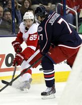 Detroit Red Wings' Danny DeKeyser, left, works for the puck against Columbus Blue Jackets' Jack Johnson in the first period of an NHL hockey game in Columbus, Ohio, Tuesday, March 11, 2014. (AP Photo/Paul Vernon)