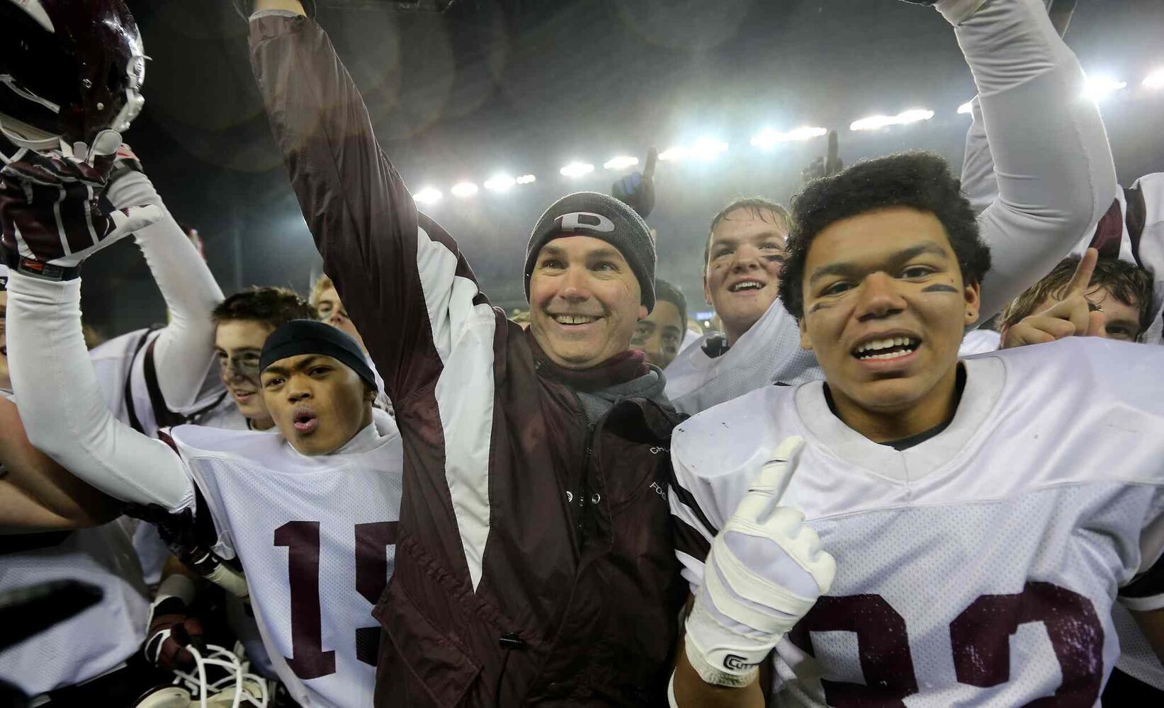 Calvin Diaz (left), head coach Peter Pura (centre) and Trevor Wright of the St.Paul's Crusaders AA football team celebrate their Free Press Bowl Championship victory over the Garden City Fighting Gophers. (Trevor Hagan / Winnipeg Free Press)