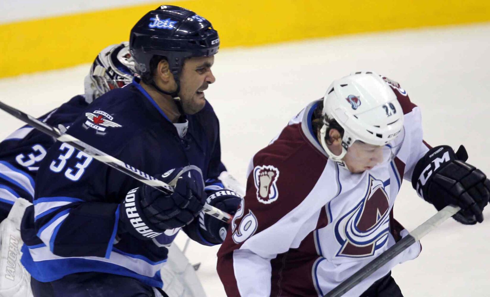 Jets defenceman Dustin Byfuglien tries to clear Colorado Avalanche skater Nathan MacKinnon from the front of the net.